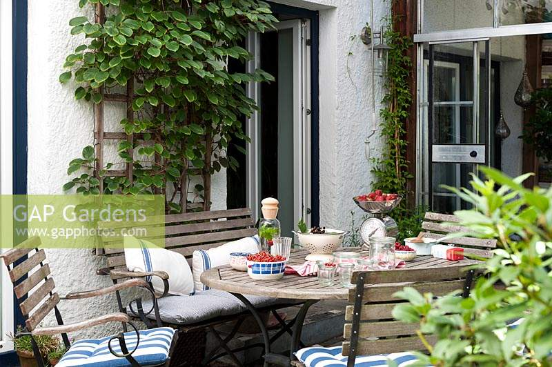 Summer terrace with seating  and table filled with harvested fruit for preserving