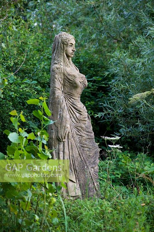 Statue of woman figure in garden.