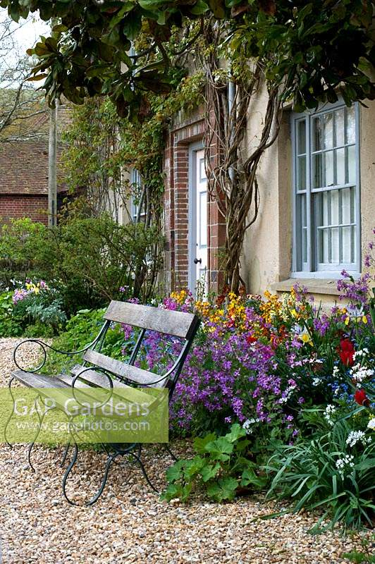 Bench in front of spring perennial border by house at Charleston, East Sussex