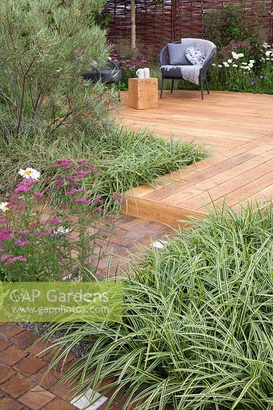 Concrete and oak setts paving with Carex 'Ice Dance' and 'Achillea millefolium 'Cerise Queen' leading to an oak decked seating area with woven willow fence in the 'Raised By Rivers' Garden at Tatton RHS Flower Show 2018