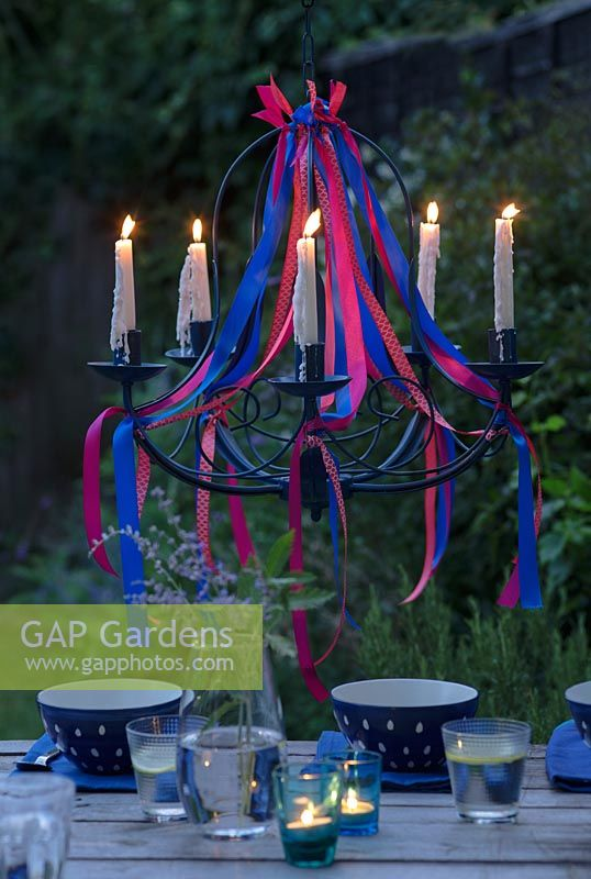 Ribbon chandelier with lit candles, hanging over a dining table at dusk.