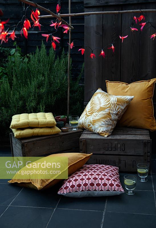 Fairylights decorated with colourful paper shapes to create beautiful decorative outdoor lighting, used here over bamboo cane supports in a seating area with fruit crates and cushions