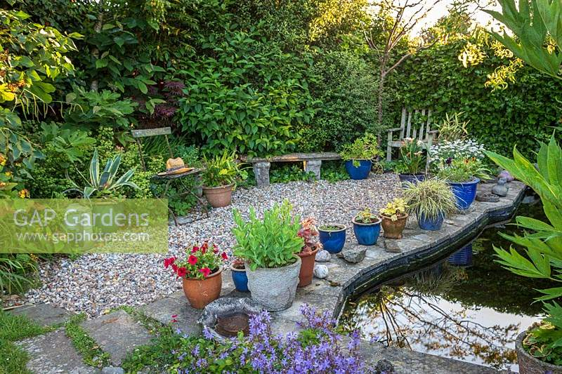 Small pond surrounded by pots and containers in Little Friars Garden, Battle, Sussex, UK.