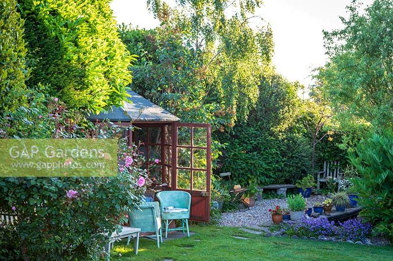 Old fashioned, wooden summerhouse with wicker chairs. Little Friars Garden, Battle, Sussex, UK.