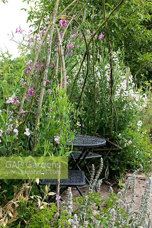 A small table and chairs is enclosed in a rustic arbour smothered in sweet peas.