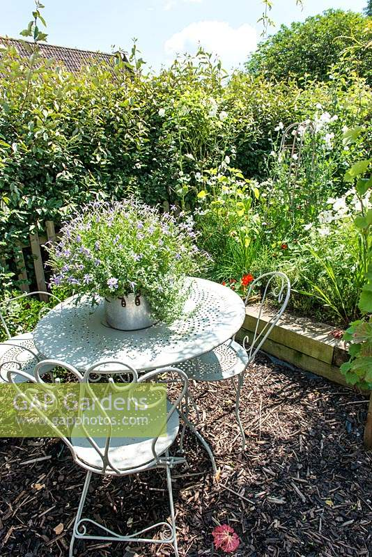 Seating area with metal furniture, bark mulch and raised bed