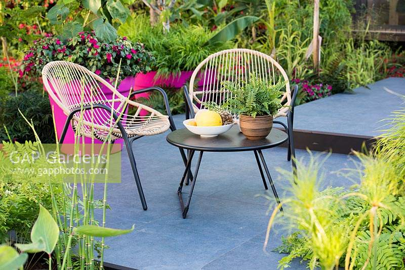 Seating area on dark paving in the garden with tender planting in pink pots. B and Q Bursting Busy Lizzie Garden at RHS Hampton Court Palace Garden Festival Show 2018