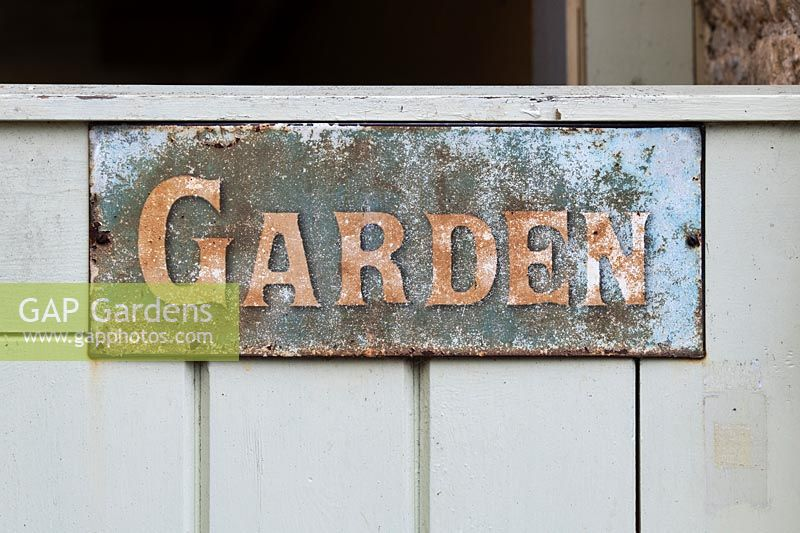 Old vintage painted garden sign on a garden gate.