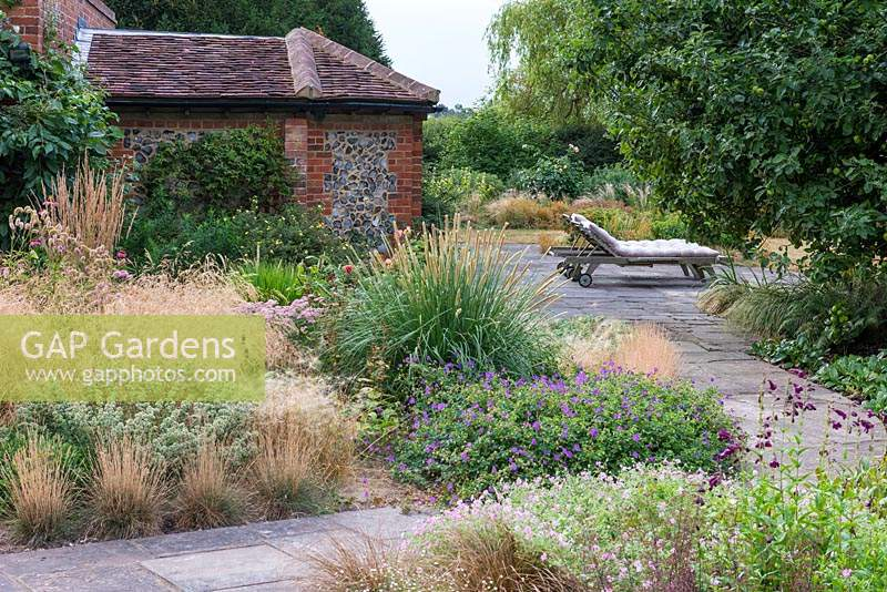 A stone terrace with loungers is reached via a straight path edged in hardy geraniums, penstemons and clumps of ornamental grasses — Deschampsia flexuosa 'Goldtau' and Pennisetum macrourum, African feather grass.