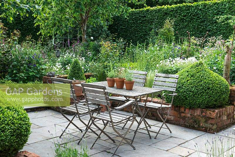 A small paved courtyard with dining table and chairs, flanked by domes of box, overlooks a box parterre planted with Bistort, hardy Geraniums, Centaurea, Foxgloves, ragged robin, Astrantias, Aquilegias and Roses with Silver birches adding height.