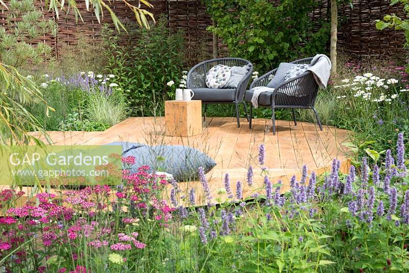 Chairs and cushions on oak decking surrounded by flowerbeds in  Raised by Rivers, RHS Tatton Park Flower Show 2018