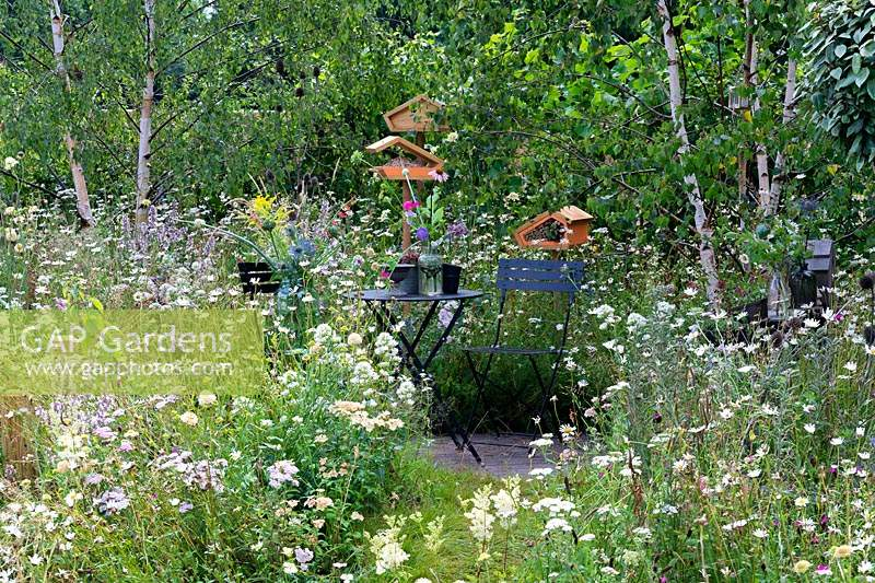 Seating area in the wild flower garden. Metal table and chairs and bird feeding tables. RHS Hampton Court Festival 2019.