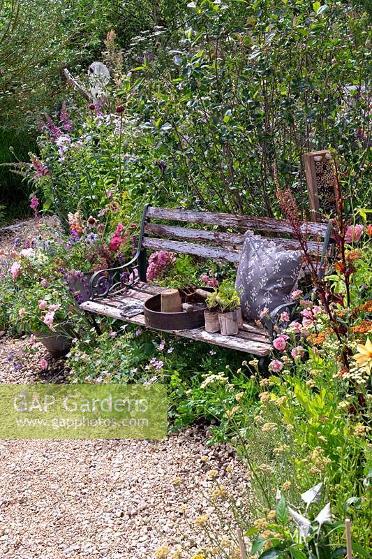 Gardening tools and cushion on rustic garden bench nestled amongst perennial planting along winding gravel path. RHS Hampton Court Festival 2019.