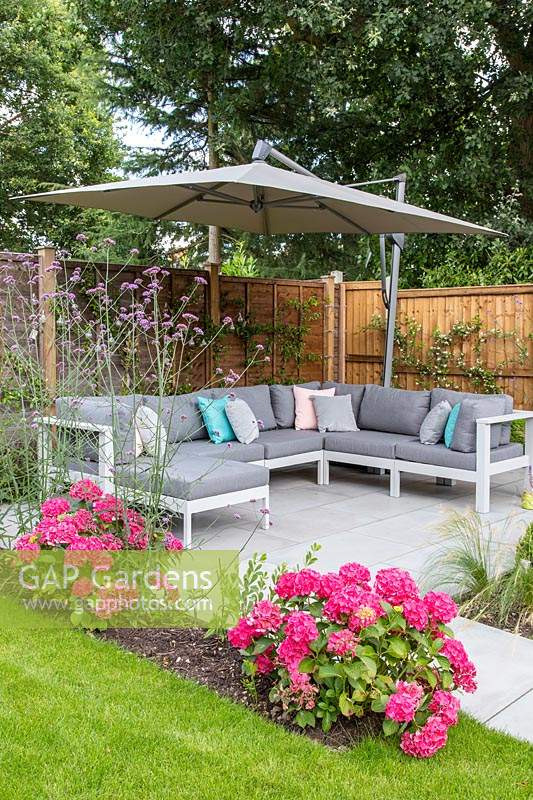 Patio area with modern corner sofa under a parasol