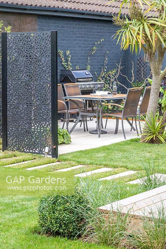 Black decorative screen dividing garden and providing privacy for seating area.