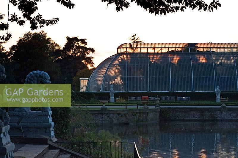 View from terrace with lion statue across pond towards Palm House at dusk