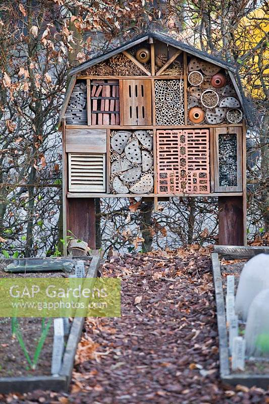 Insect house on wooden supports in a vegetable garden
