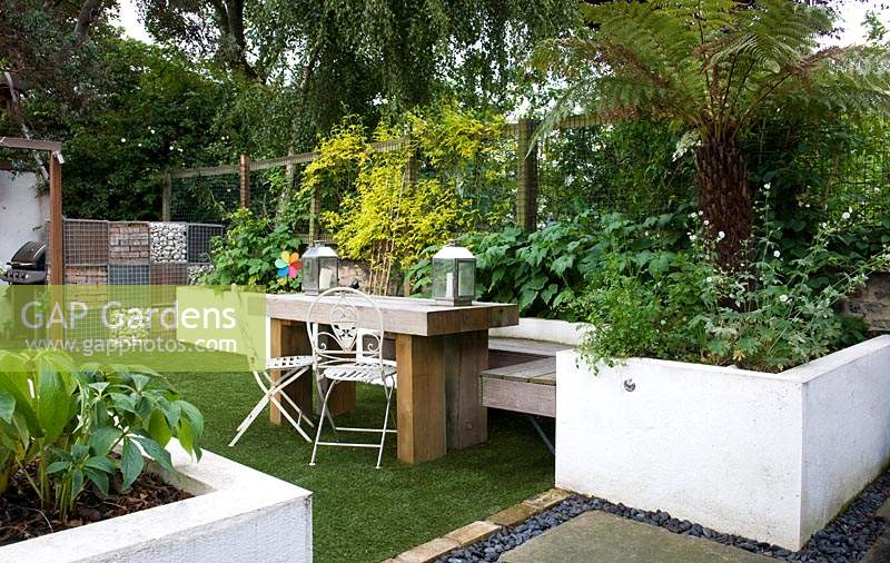 View over garden, with white raised borders and dining table.