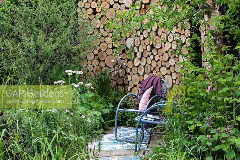 The Art of Viking Garden. A cool woodland seating area, sheltered by a natural log wall and planted with moisture-loving plants. Sponsor: Viking Cruises.