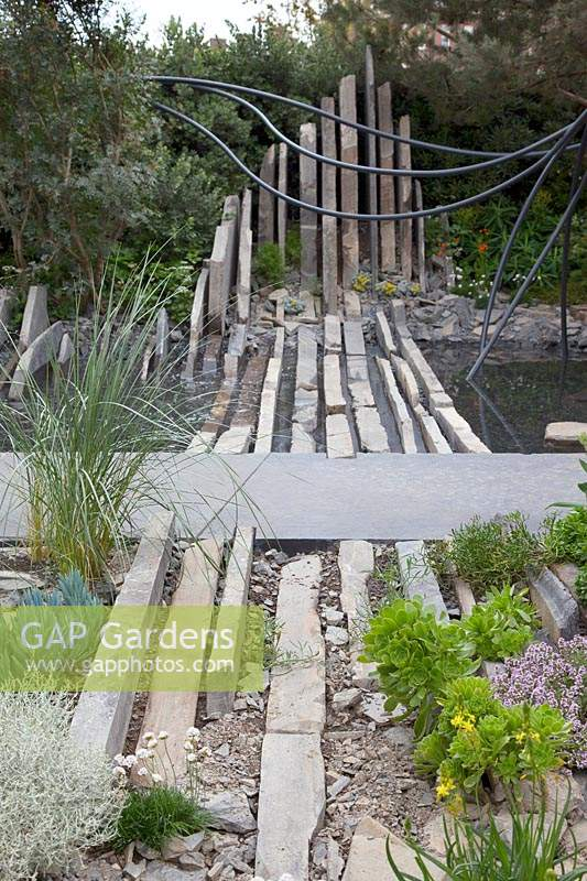 Facebook: Beyond The Screen, large slabs of Caithness stone represent rock formations in this coastal themed garden, whilst the planting includes Senecio mandraliscae, Leucophyta brownii, Ammophila arenaria, Armeria maritima 'Alba' Thymus vulgaris and Aeonium arboreum. Sponsor: Facebook.