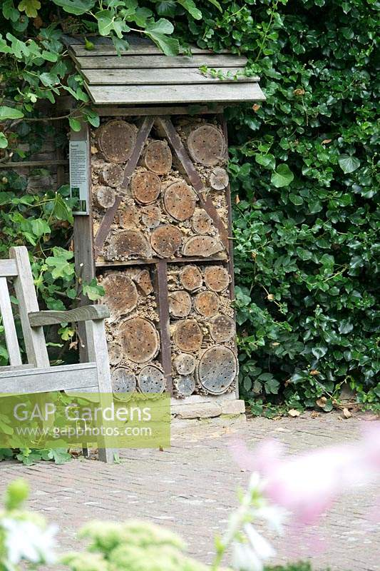 Insect hotel with roof, against a wall by path and bench