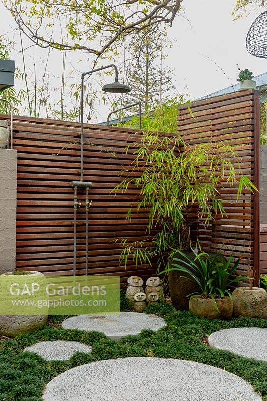 Corner of a garden next to a painted brick fence, featuring a timber slat screen with an outdoor shower, a stone carved Indonesia pot, a family group of sculptures, a large glazed water bowl, semi rustic stone pots, concrete circular cast in situ stepping stones in amongst a thick planting of mini Mondo grass.