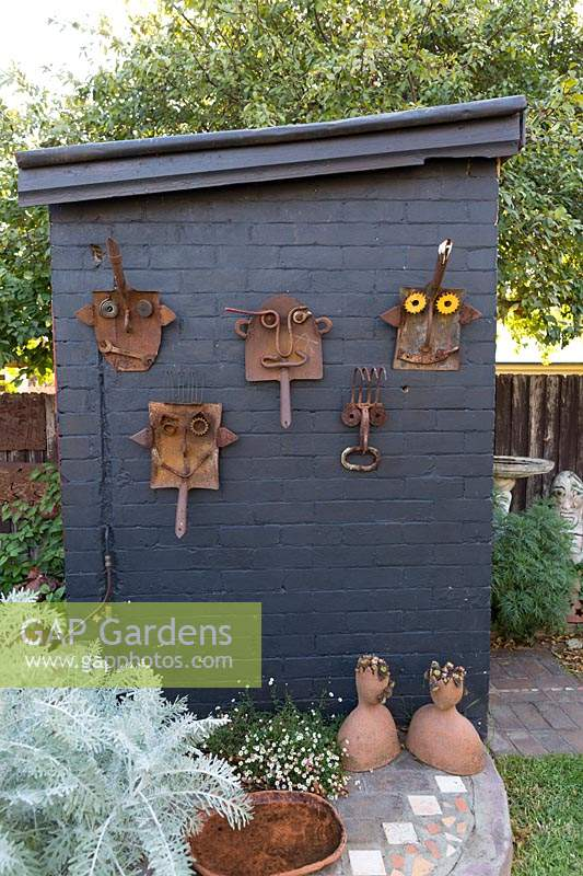 Whimisical wall decorations made from old rusty, spade and shovel heads and pieces scrap metal mounted on a grey painted outhouse wall in a backyard, with a planting of Jacobaea maritima, Dusty Miller with silver, grey foliage.