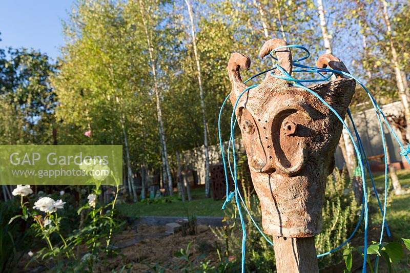 A stylised pottery head being used a tomato stake topper and twine holder in a vegetable garden.