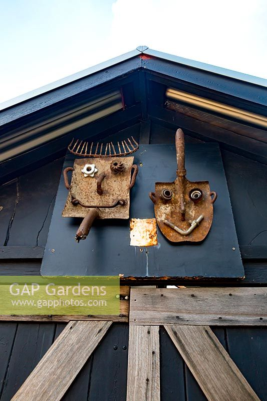 An outhouse that is decorated with two bespoke spadehead sculptures.