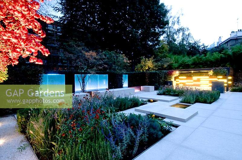 View across modern city garden, illuminated by contemporary lighting at dusk.