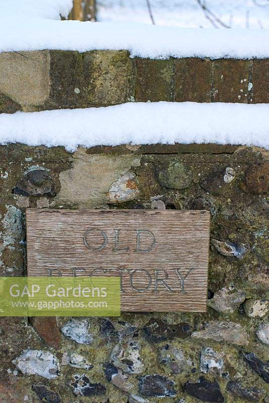 Snow on the old flint wall in late February with wooden house sign. The Old Rectory, Suffolk, UK