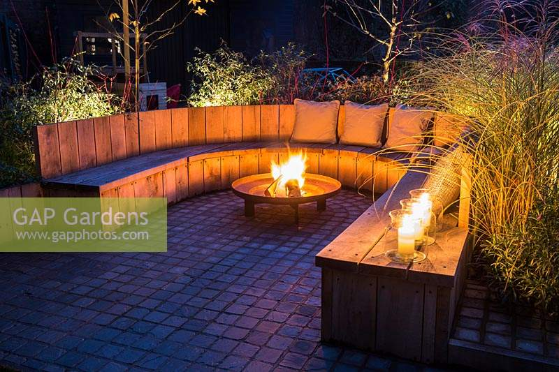 Seating area with fire pit and round wooden bench surrounded by Miscanthus sinensis 'Morning Light' - eulalia and Cornus alba 'Sibirica' - Siberian dogwood, AGM at night in Autumn.