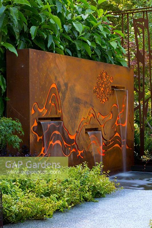 Freestanding rusty coreten steel fountain, featuring internally lit laser cut patterns reresenting mountains and clouds, with three rills behind pale grey stepping stones.