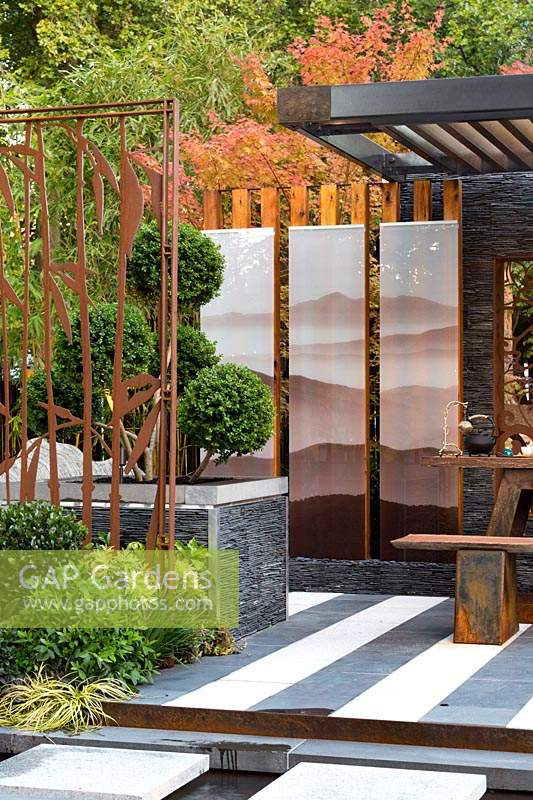A cloud pruned conifer in a raised planter box with stacked stone panels behind a rusty steel screen with a cutout bamboo motif in front of three glass screens