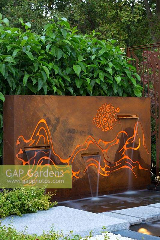 Freestanding rusty coreten steel fountain, featuring internally lit laser cut patterns reresenting mountains and clouds, with three rills behind pale grey stepping stones with a screen planting of Magnolias.