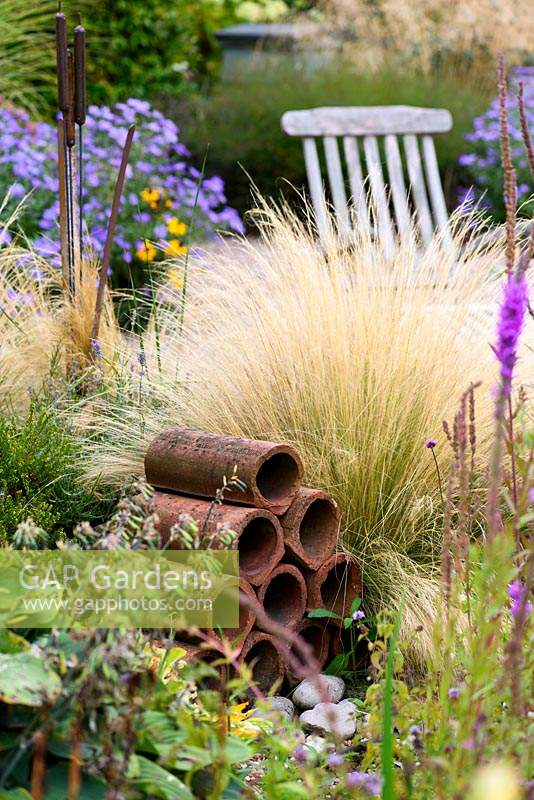 Clay drainage pipes amongst Stipa tenuissima and asters.