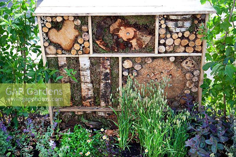 Tiered insect hotels made from recycled materials in the 'Living in Sync' garden at BBC Gardener's World Live 2017