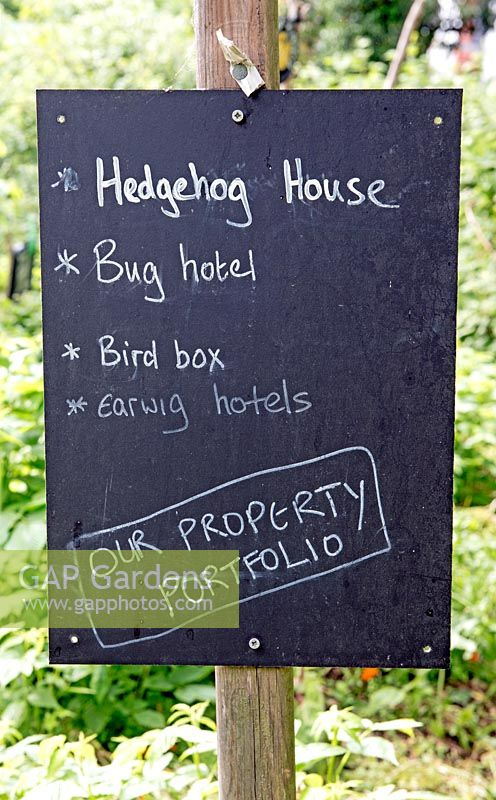 Board advertising property portfolio for Hedgehog House, Bug Hotel, Bird Box and Earwig Hotel, Priory Common Orchard Community Garden, London Borough of Haringey.