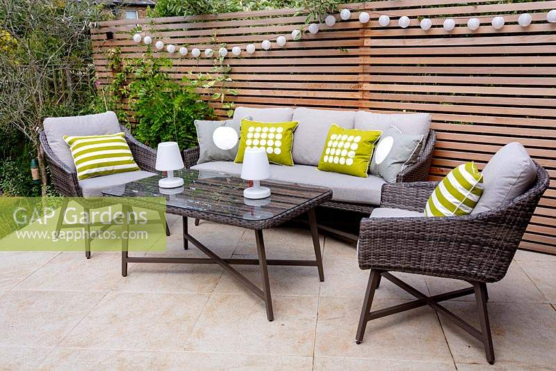 London contemporary garden with modern garden sofa, chairs and table on patio with cedar batten trellis fencing behind.