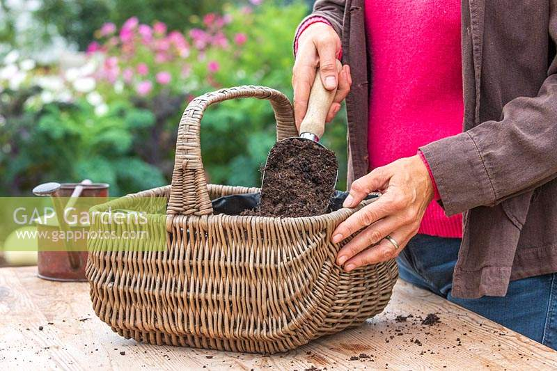 Woman adding compost to the basket using a metal scoop.