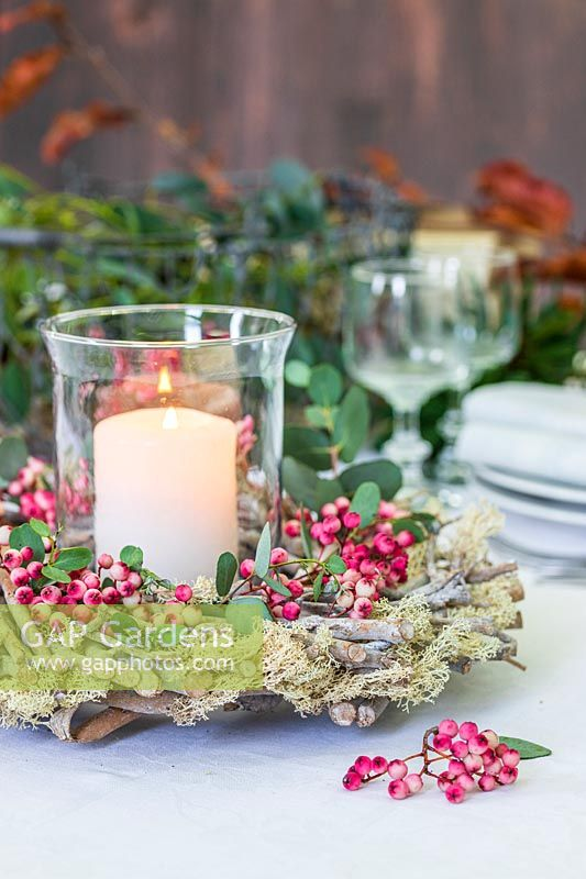 Table decoration comprised of: pillar candle in storm lantern surrounded by wooden wreath with moss, Sorbus - Rowan - berries and Eucalyptus foliage