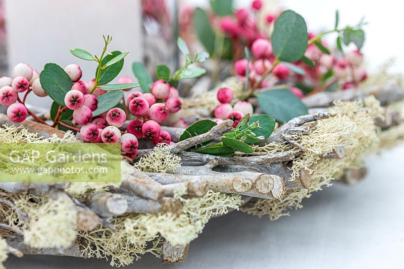 Detail of table arrangement with wooden wreath decorated with pink Sorbus - Rowan - berries amd Eucalyptus foliage