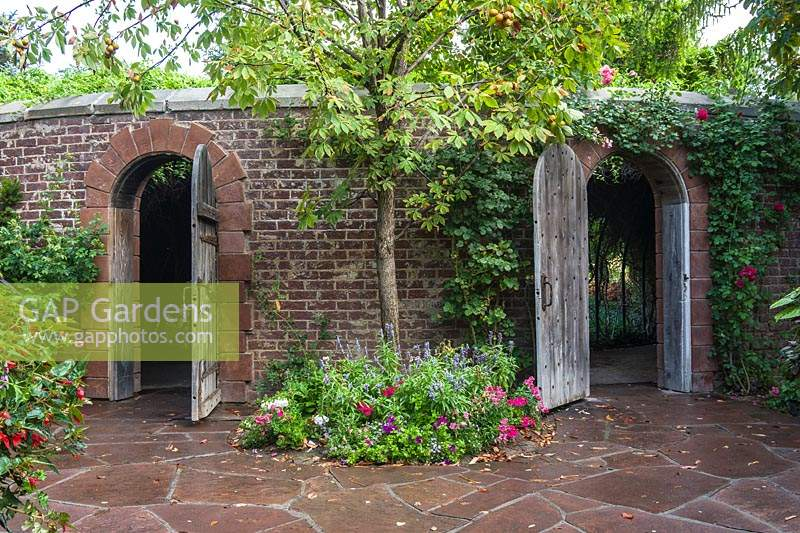 Brick walls with stone arches with wooden gates. Wall has Rosa - Climbing Rose over entrance and Aesculus glabra - Ohio Buckeye - underplanted between the gates