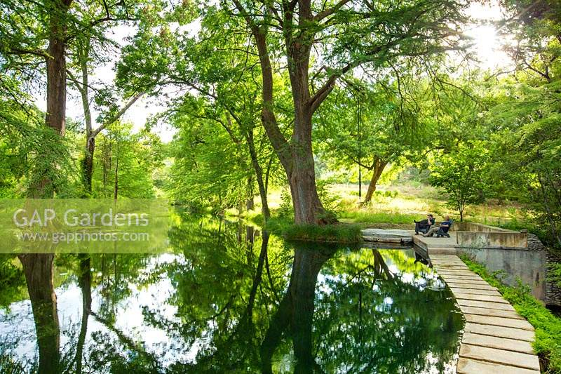 Reflections in the lake at Mill Creek Ranch in Vanderpool, Texas designed by Ten Eyck Landscape Inc, July.