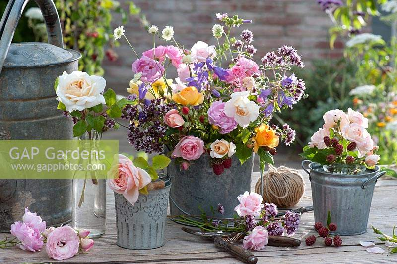Containers of mixed bouquet of roses, oregano, bluebells and fragrant scabious.