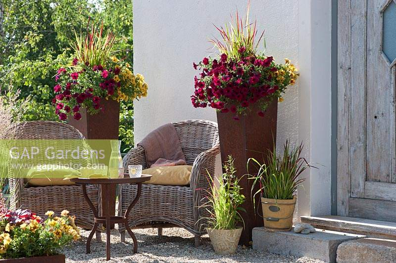 Petunia Beautical 'Bordeaux' 'Caramel' and Japanese red grass 'Red Baron' in rust pots on a gravel terrace, seating area with wicker chairs and a rusty table