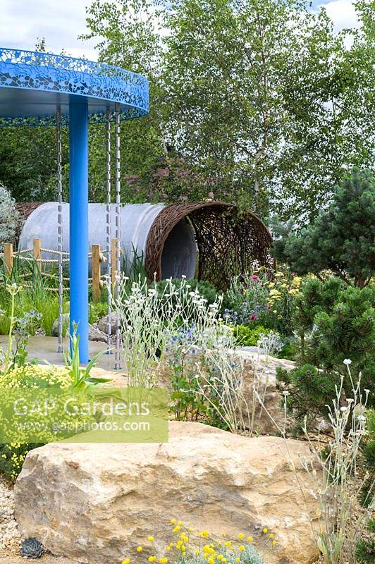 Blue rainfall pavilion with raincatchers and gravel garden with Lychnis coronaria 'Alba', Santolina chamaecyparissus and Pinus mugo in foreground. The Thames Water Flourishing Future Garden - RHS Hampton Court Palace Garden Festival 2019