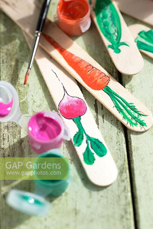 Painting ice lolly sticks to make plant labels for vegetables