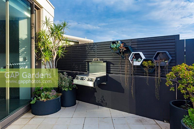 Corner of a rooftop garden with a group of pots and a wall mounted barbecue.