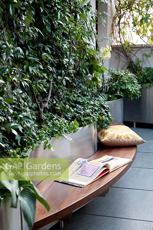 Built-in wooden bench seat around curving silver steel planters